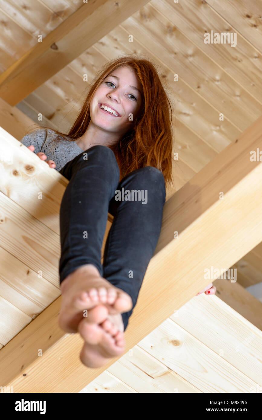 Mädchen sitzt unterm Dach, Innenausbau Dachgeschoss, Boden legen, Holzhaus, Bayern, Deutschlaned - Stock Image