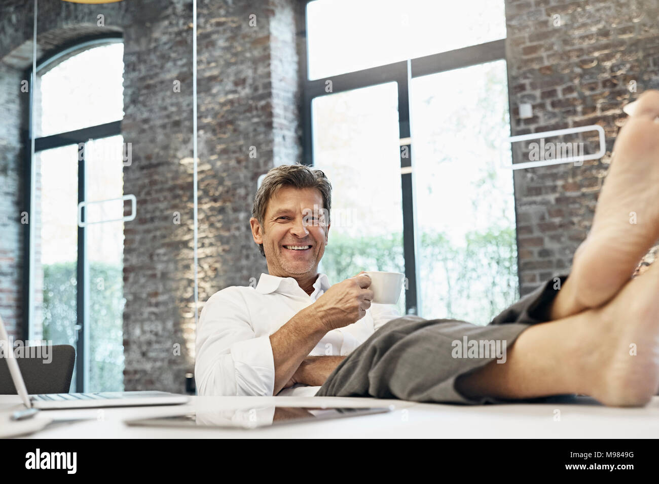 Barefooted businessman relaxing and drinking coffee in modern office - Stock Image