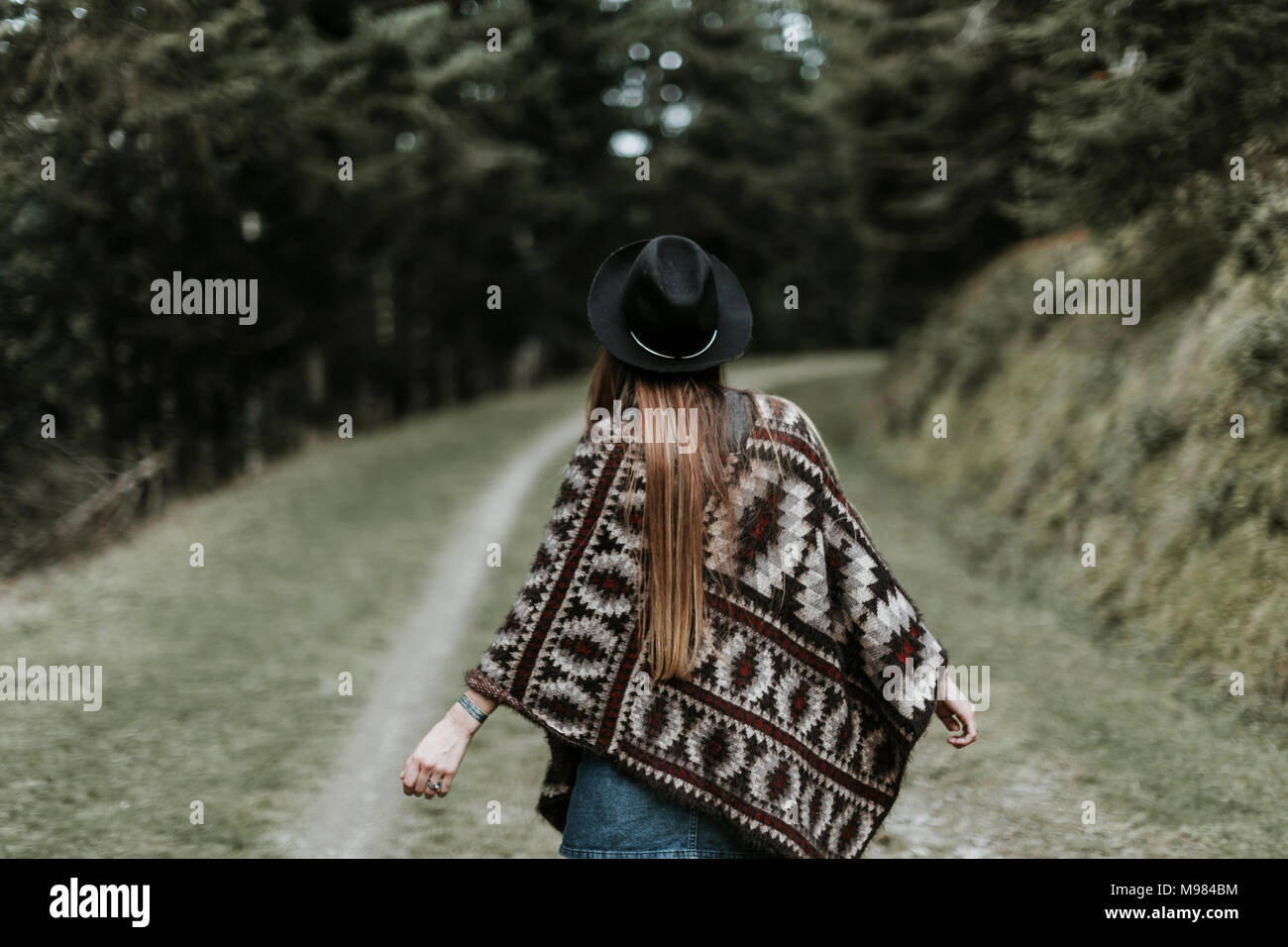 Back view of fashionable young woman wearing hat and poncho in nature - Stock Image