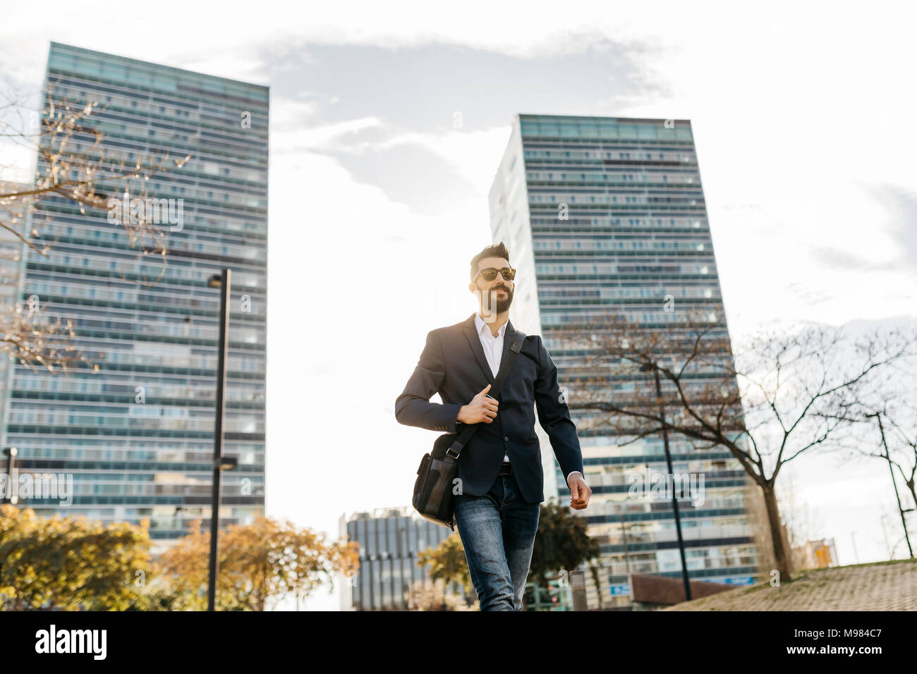Businessman wearing sunglasses walking outside office building - Stock Image