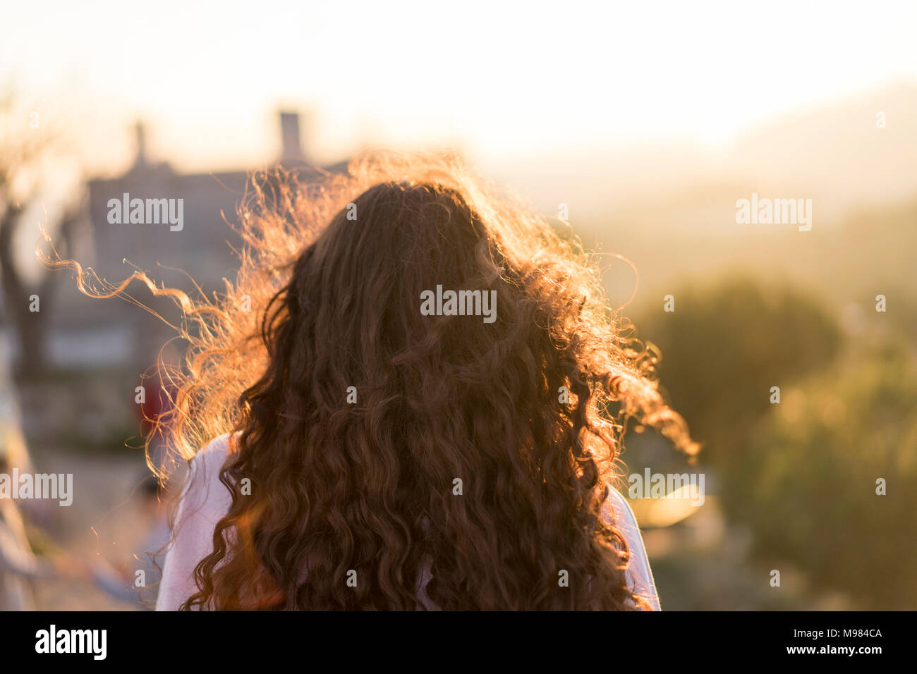 Back View Of Young Woman With Long Curly Hair At Sunset Stock Photo
