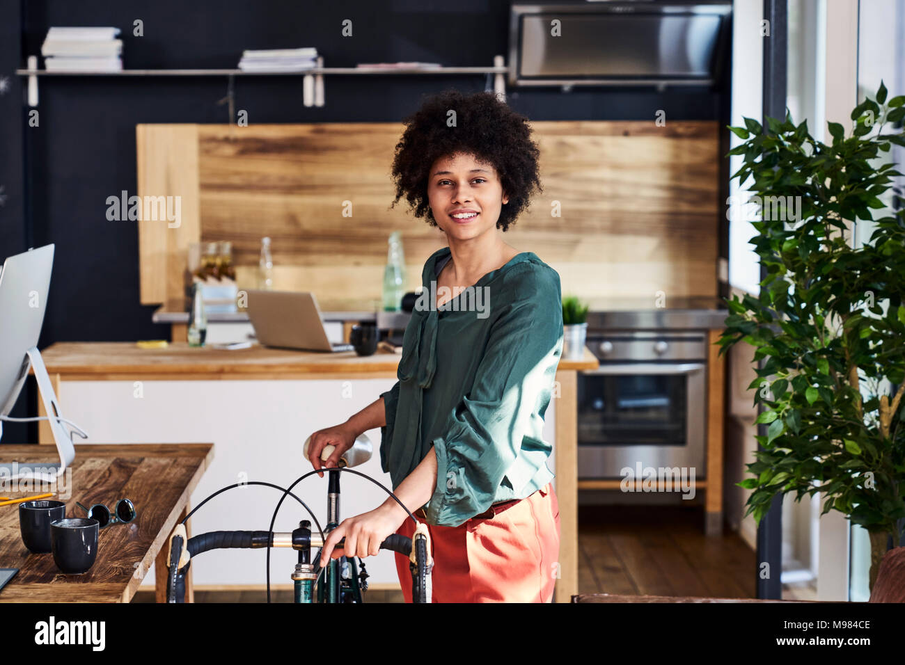 Portrait of smiling young woman with bicycle in modern office - Stock Image