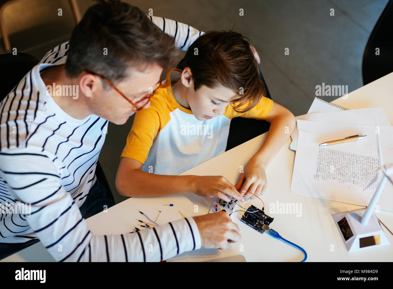 Father and son assembling a construction kit with wind turbine model - Stock Image