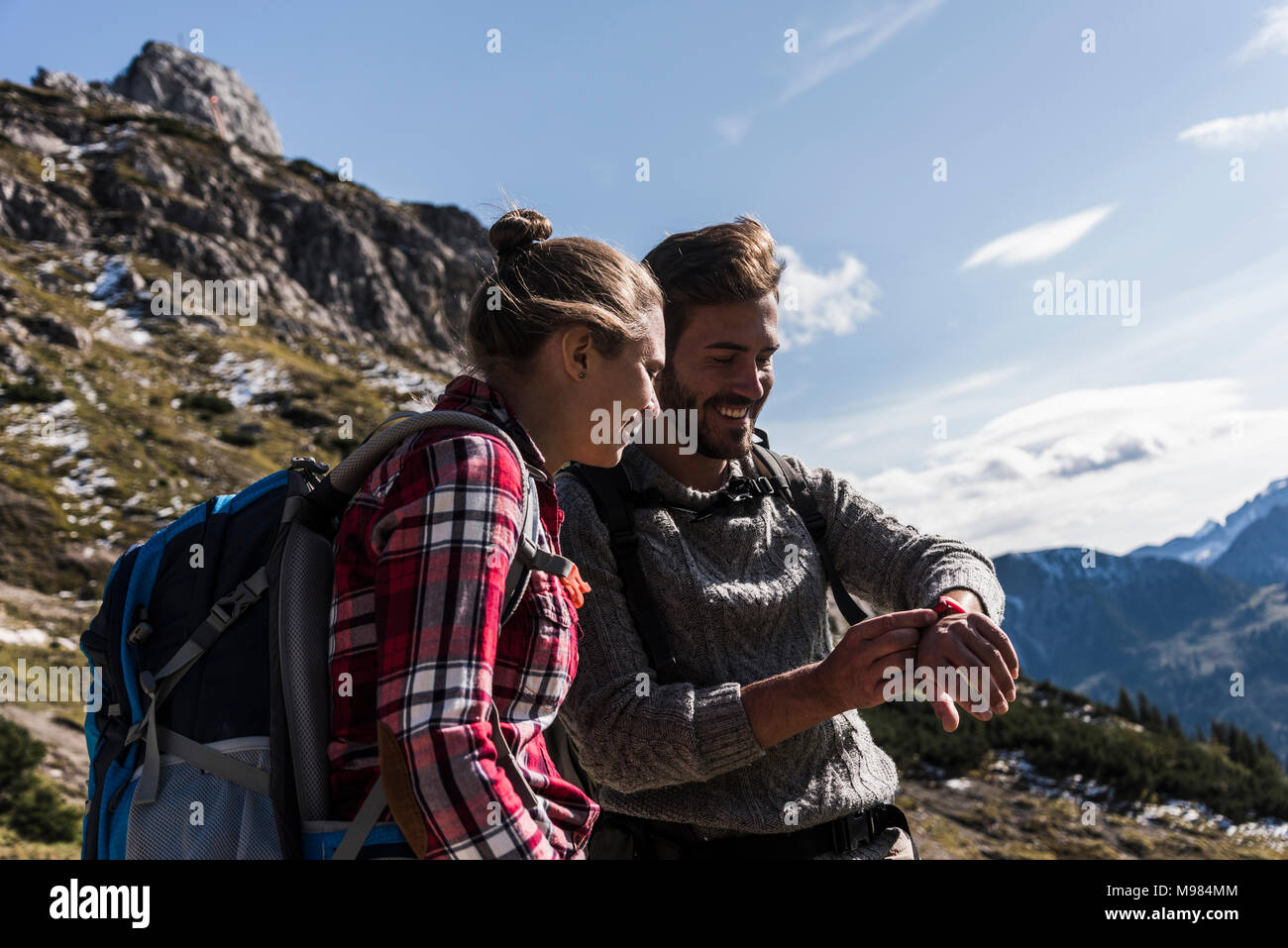 Austria, Tyrol, smiling young couple looking at watch in mountainscape - Stock Image