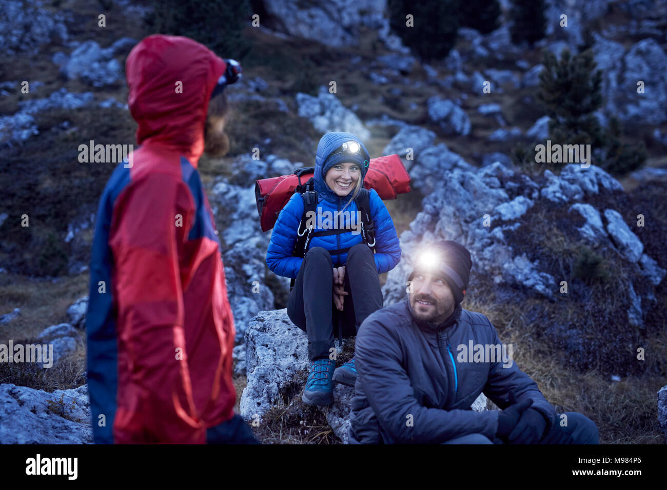 Smiling mountaineers wearing headlamps in the mountains at dusk - Stock Image