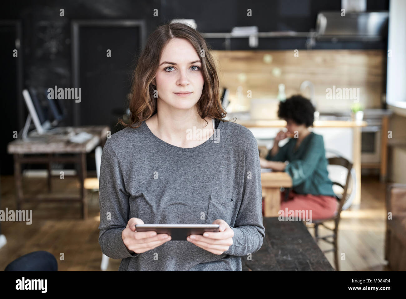 Portrait of young woman holding tablet in modern office - Stock Image