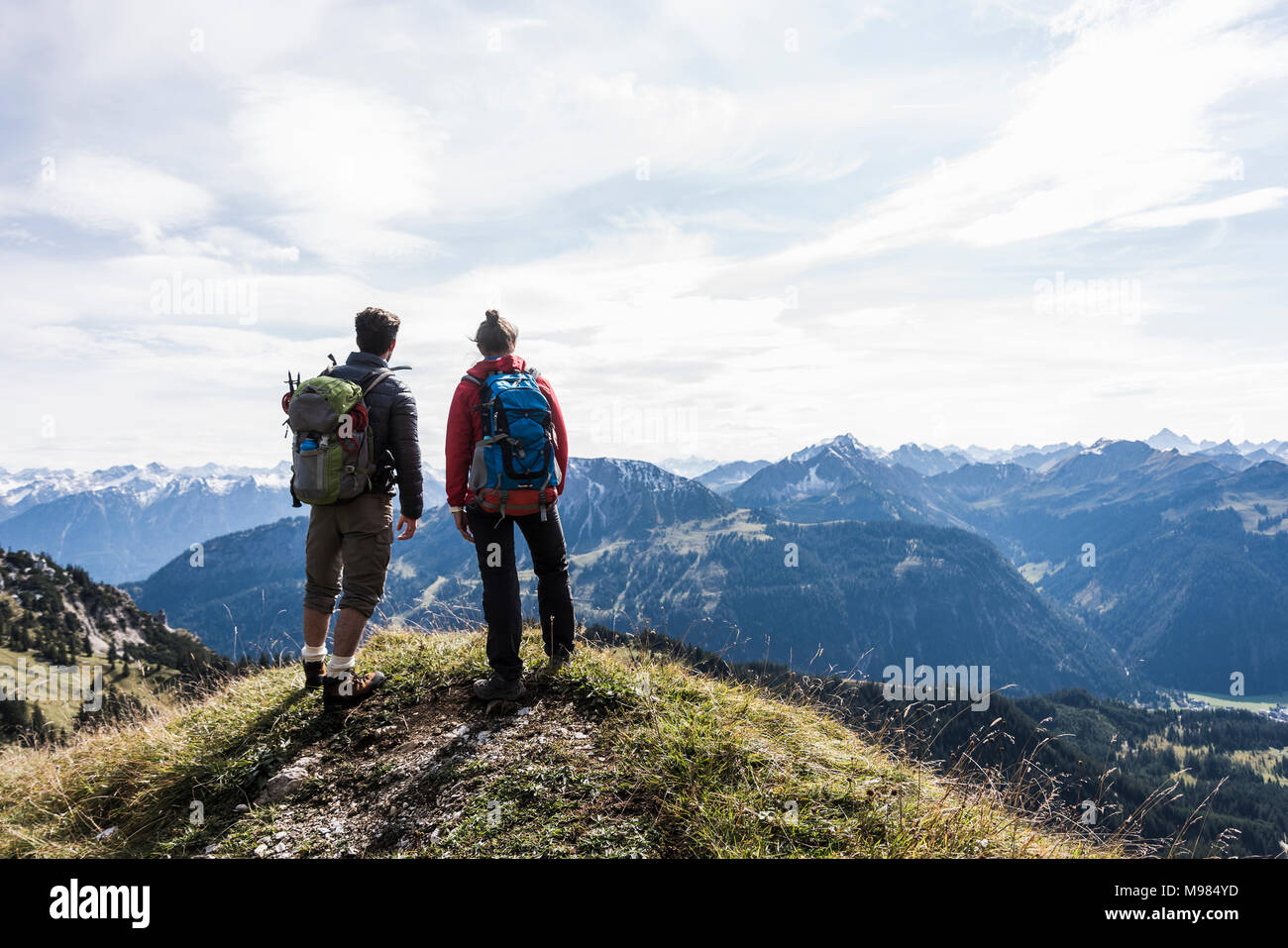 Austria, Tyrol, young couple standing in mountainscape looking at view - Stock Image