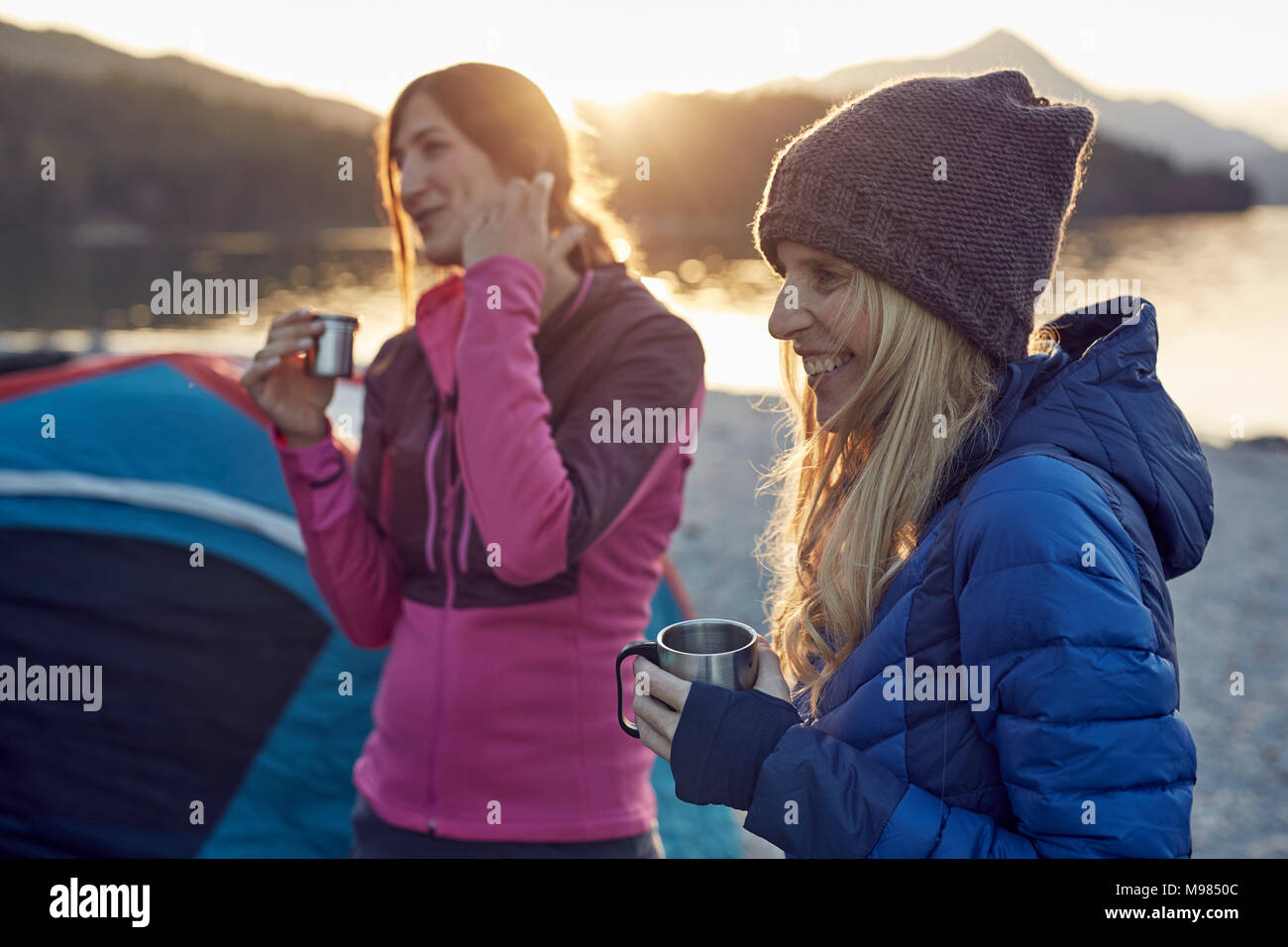 Two female friends at tent holding mugs - Stock Image