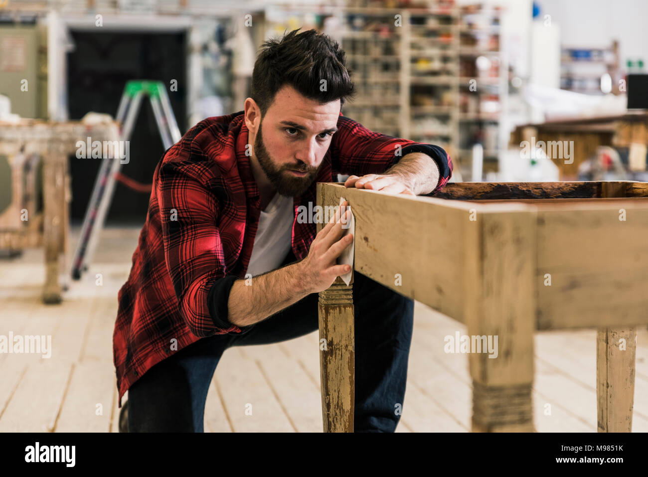 Man treating wood in workshop with sand paper - Stock Image