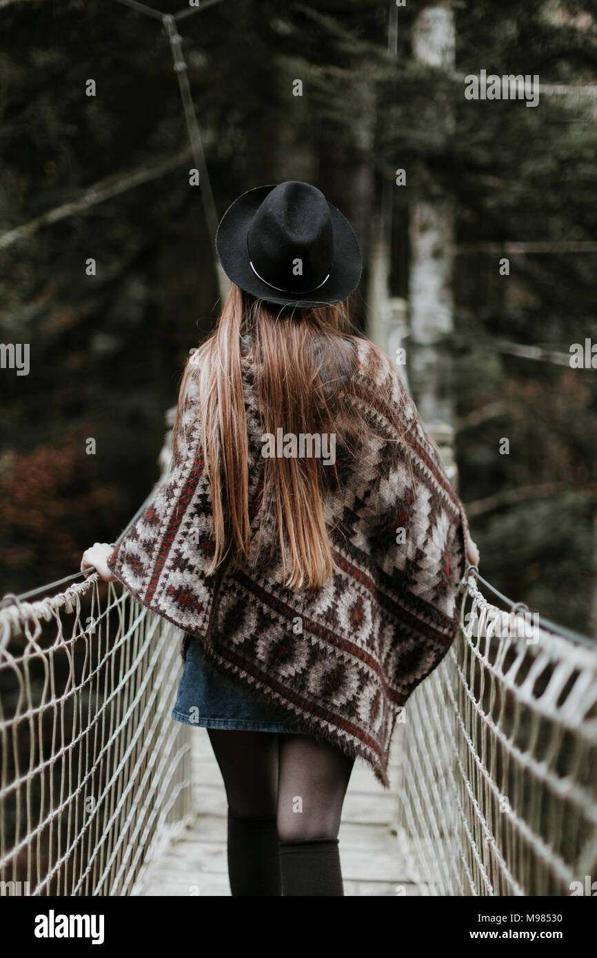 Back view of fashionable young woman wearing hat and poncho walking on suspension bridge - Stock Image