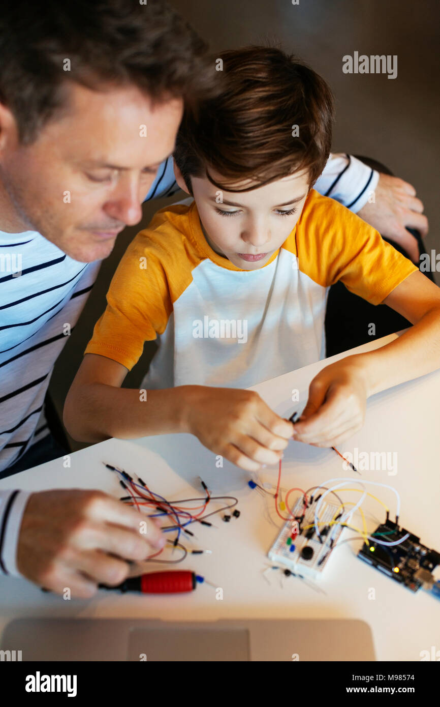 Father and son assembling an electronic construction kit - Stock Image