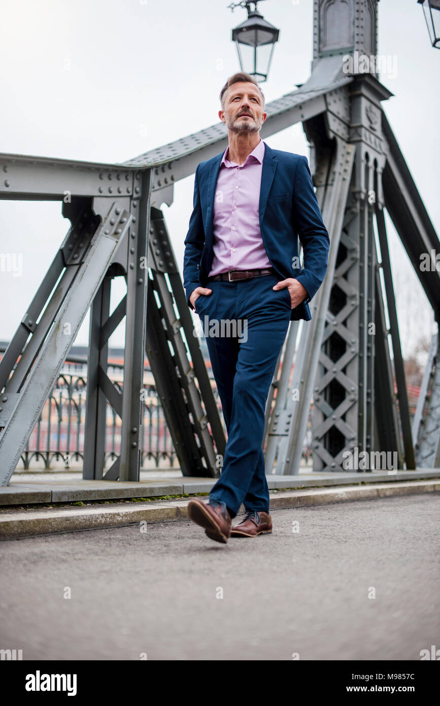 Stylish mature businessman wearing blue suit walking on bridge - Stock Image