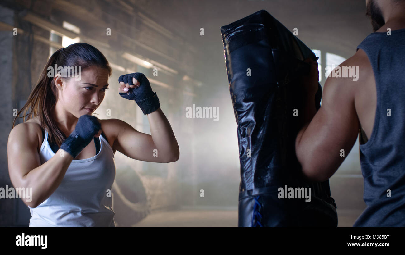 Athletic Woman Trains Her Punches on a Punching Bag that Her Partner/ Trainer Holds. She's Strong and Gorgeous Woman. They Workout in a Gym. - Stock Image