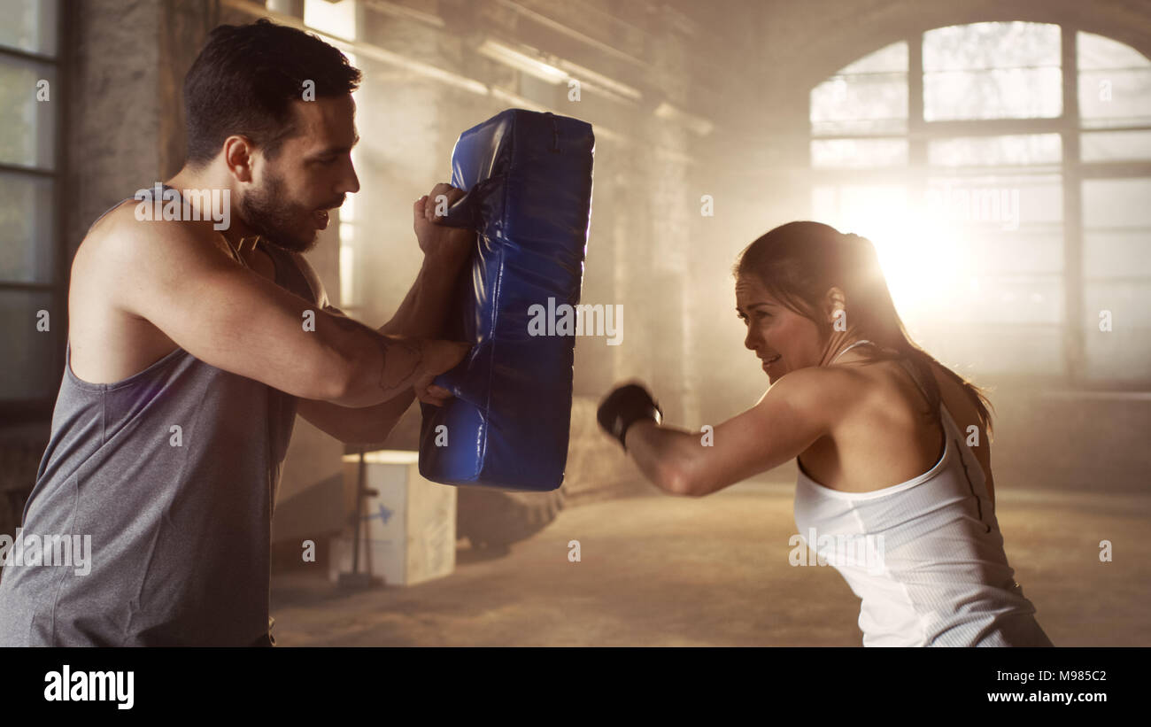 Athletic Woman Trains Her Punches on a Punching Bag that Her Partner/ Trainer Holds. She's Professional Fighter and Works out in a Hardcore Gym. - Stock Image