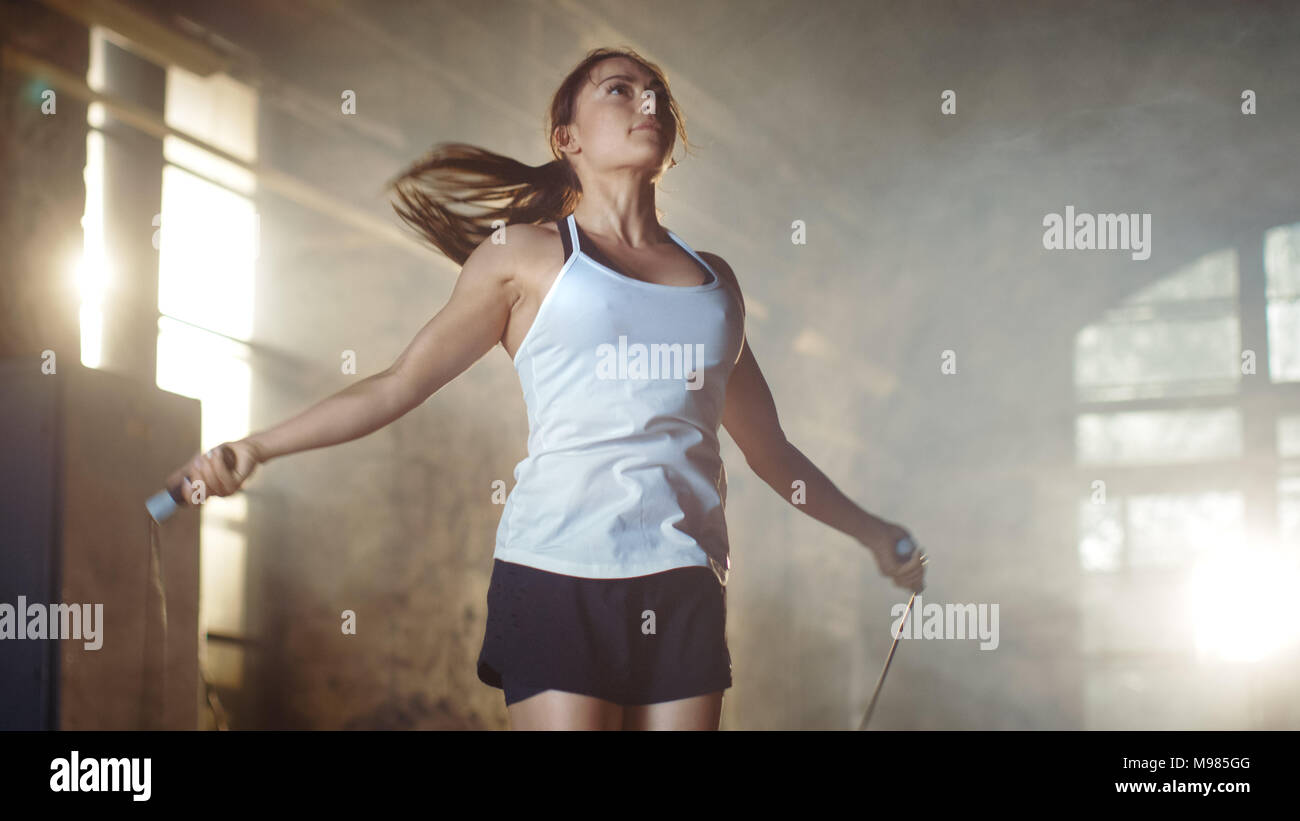 Athletic Beautiful Woman Exercises with Jump / Skipping Rope in a Gym. She's Doing Part of Her Intense Fitness Training. - Stock Image