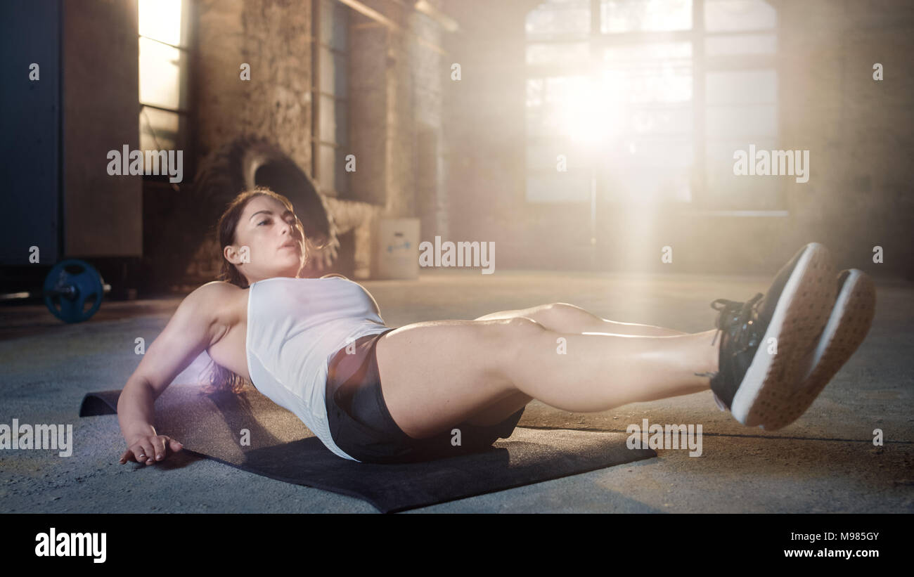 Athletic Beautiful Woman Does Crunches / Sit Ups /  Abdominal Exercises as Part of Her Cross Fitness, Bodybuilding Gym Training Routine. - Stock Image