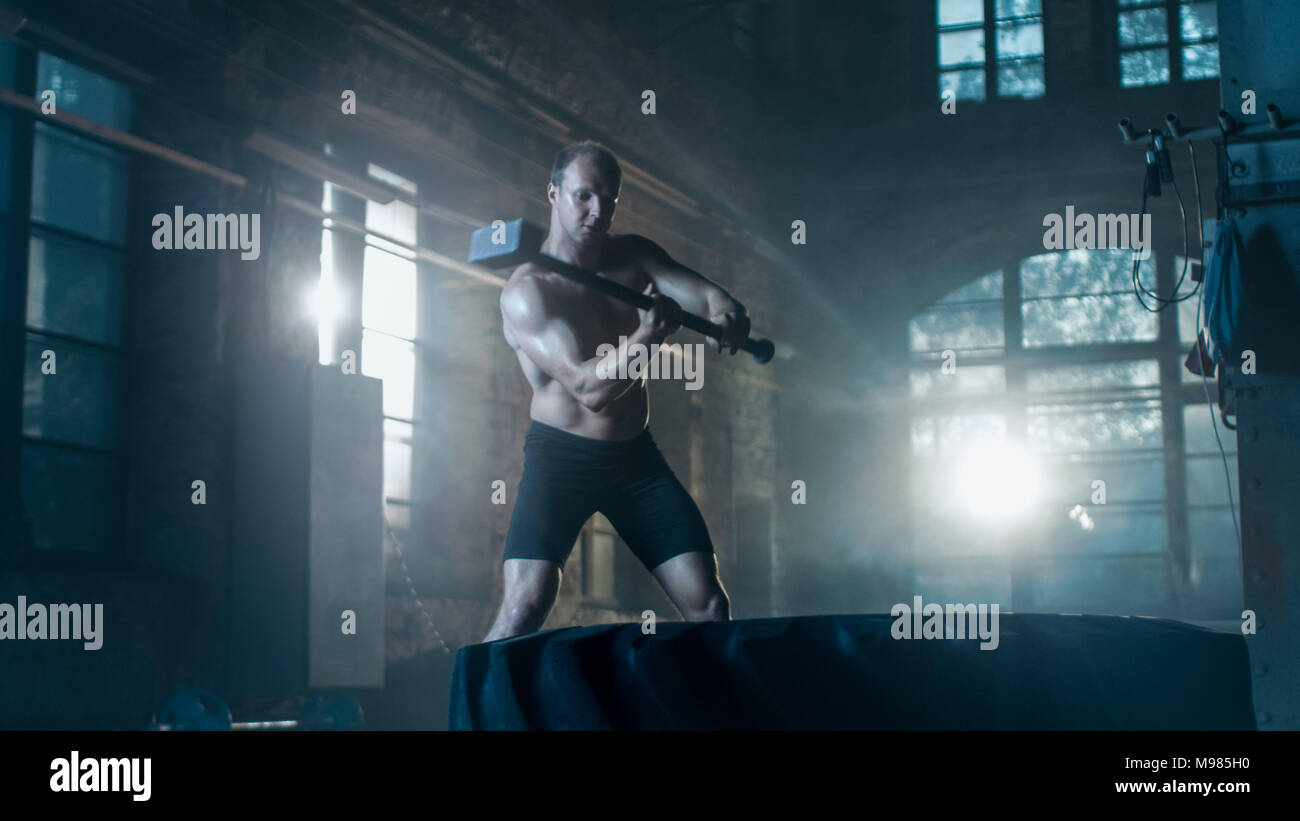 Strong Muscular Man Hits Tire with a Sledgehammer as Part of His Cross Fitness Bodybuilding Gym Training. - Stock Image