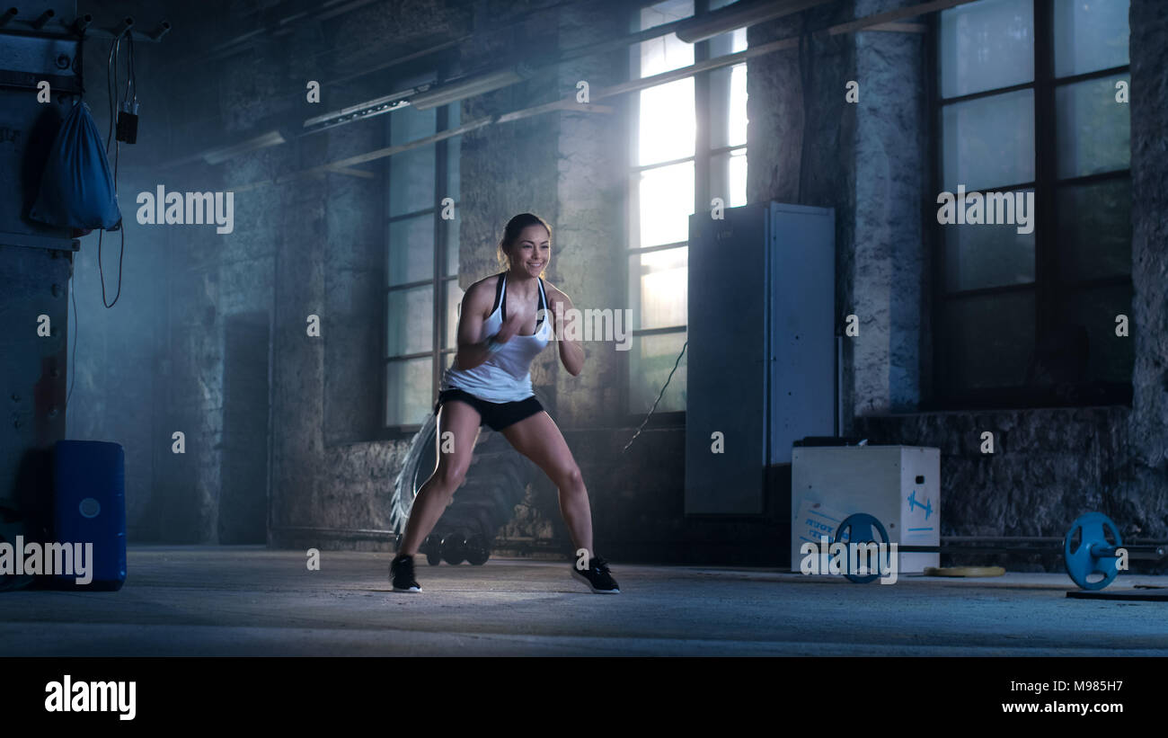 Fit Athletic Woman Does Footwork Running Drill in a Deserted Factory Remodeled into Gym. Cross Fitness Exercise/ Workout Aimed at Strengthening Legs,  - Stock Image