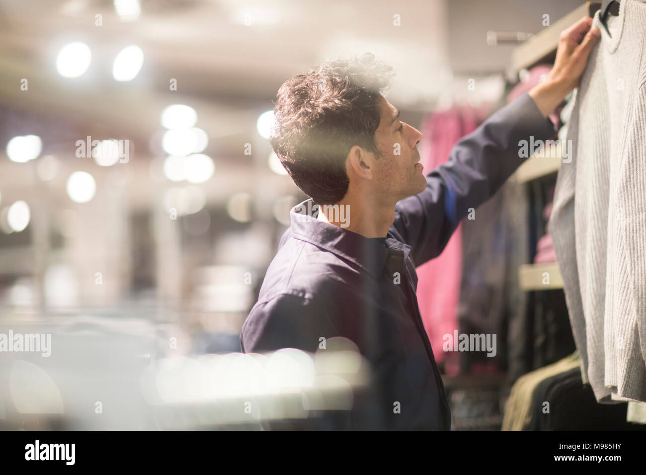 Man choosing clothes in shop - Stock Image