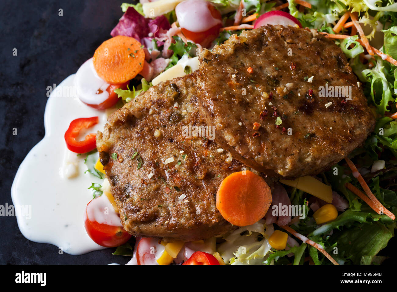 Veggie burger with lettuce, vegetables and yoghurt sauce - Stock Image