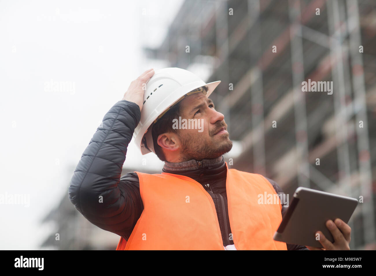 Man with tablet wearing safety vest and hard hat at construction site - Stock Image