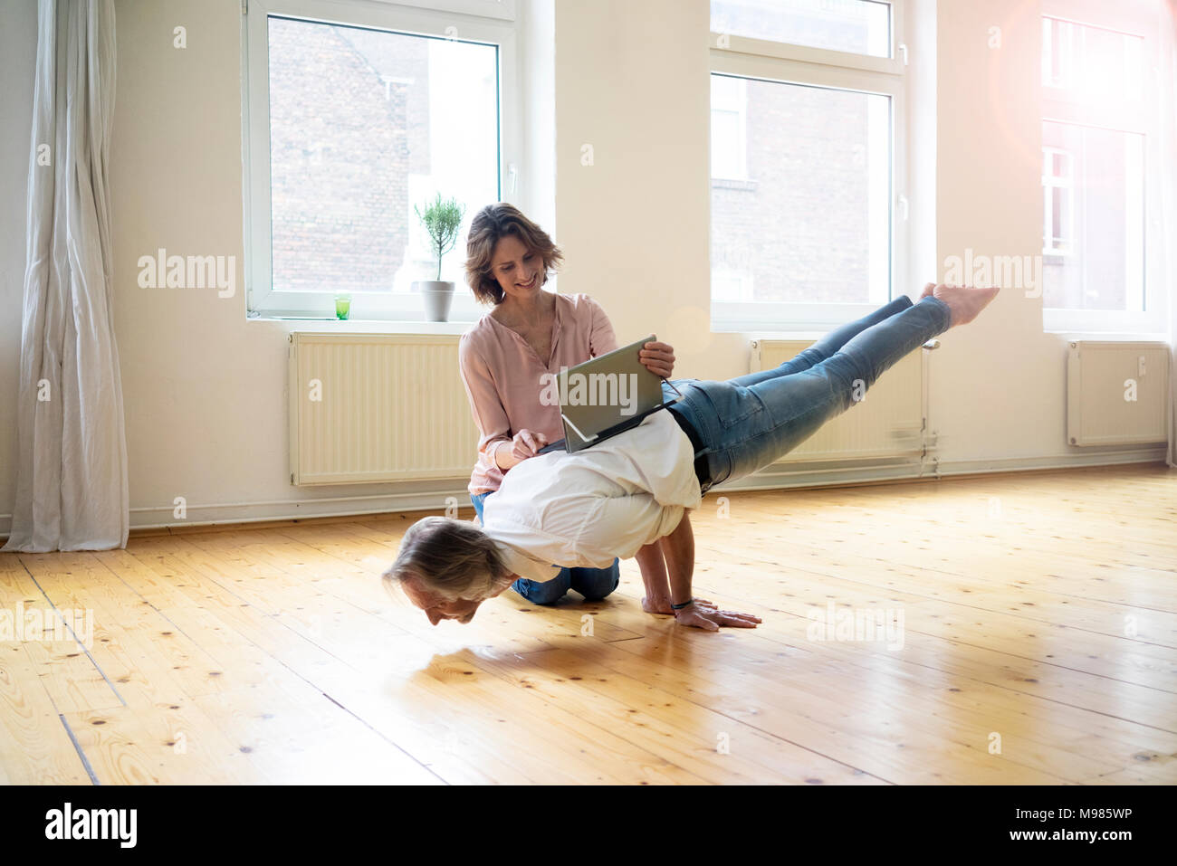 Mature woman using tablet on back of man doing a handstand - Stock Image