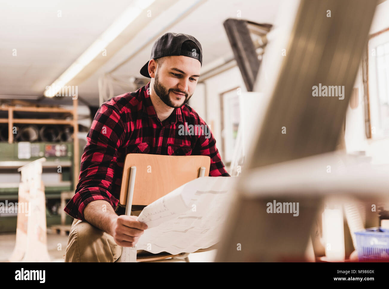 Worker looking at draft in workshop - Stock Image