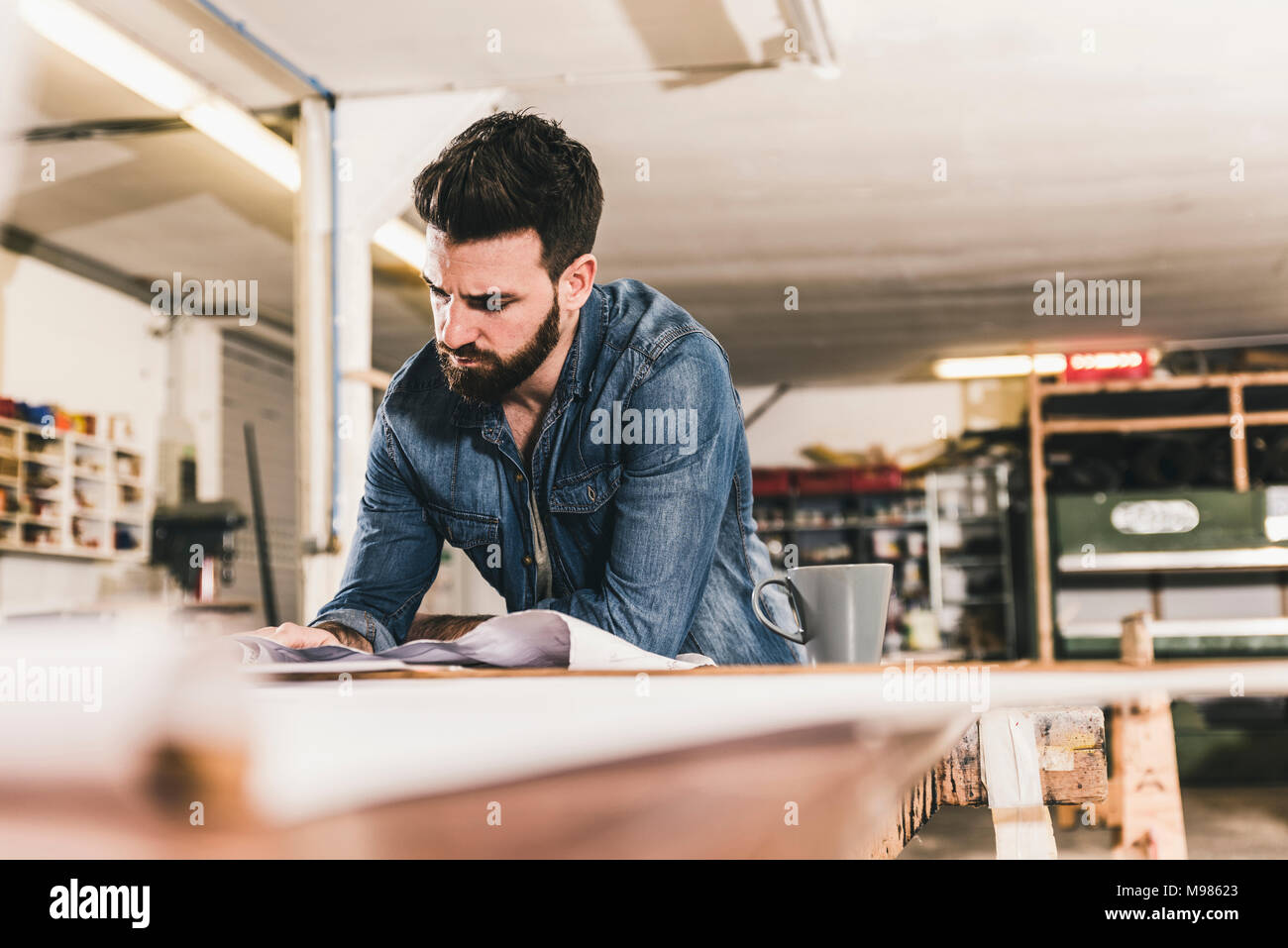 Man looking at draft in workshop - Stock Image