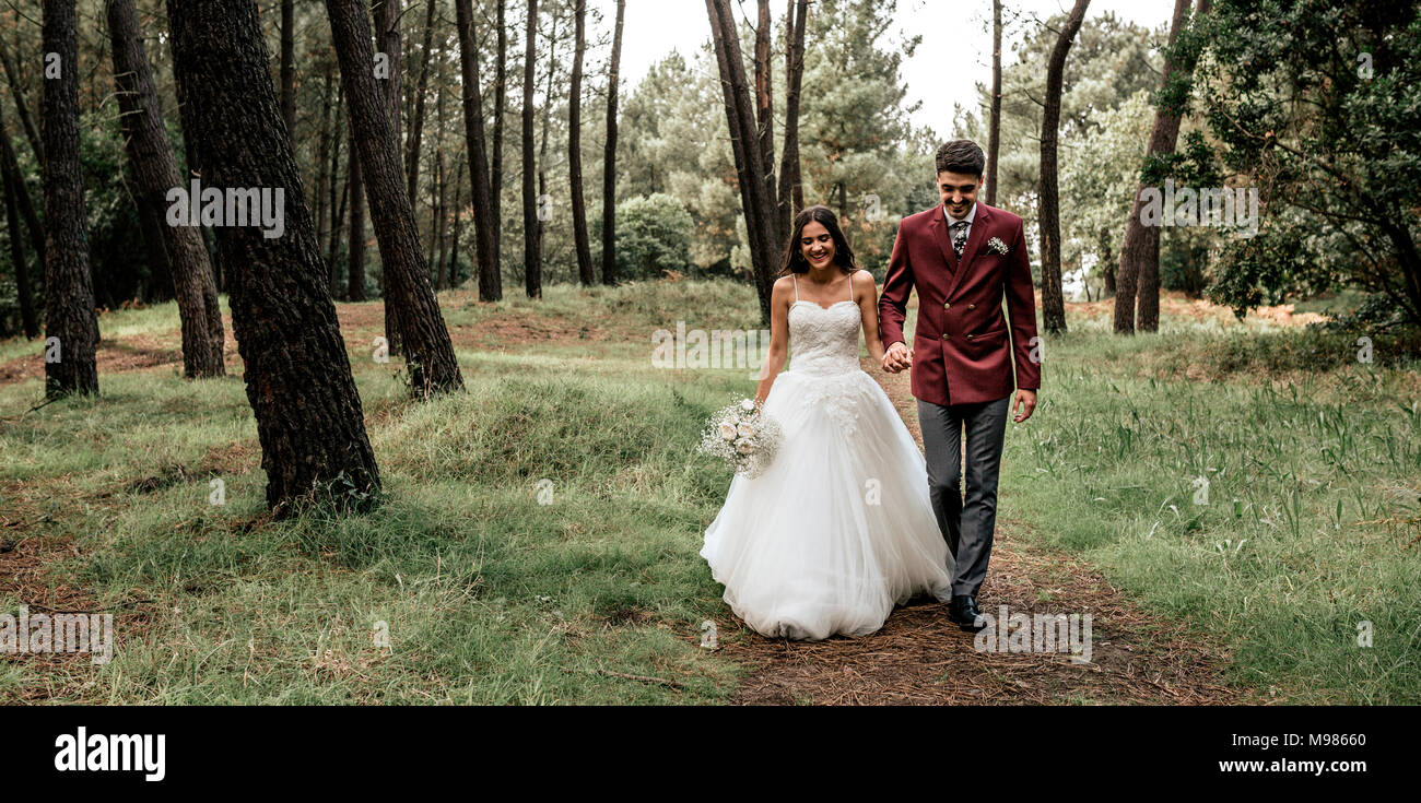 Happy bride and groom walking in forest - Stock Image