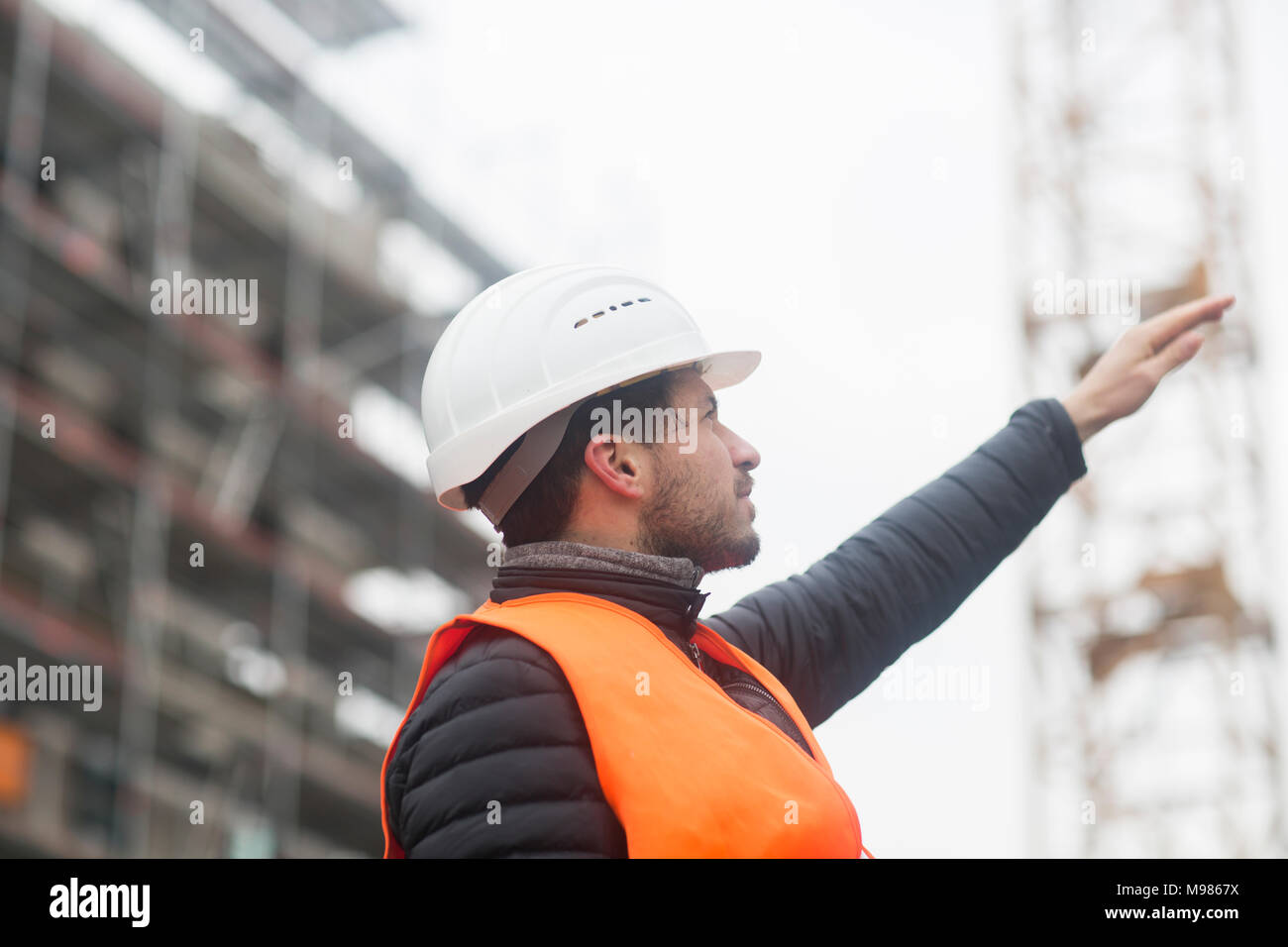 Man with wearing safety vest and hard hat at construction site - Stock Image