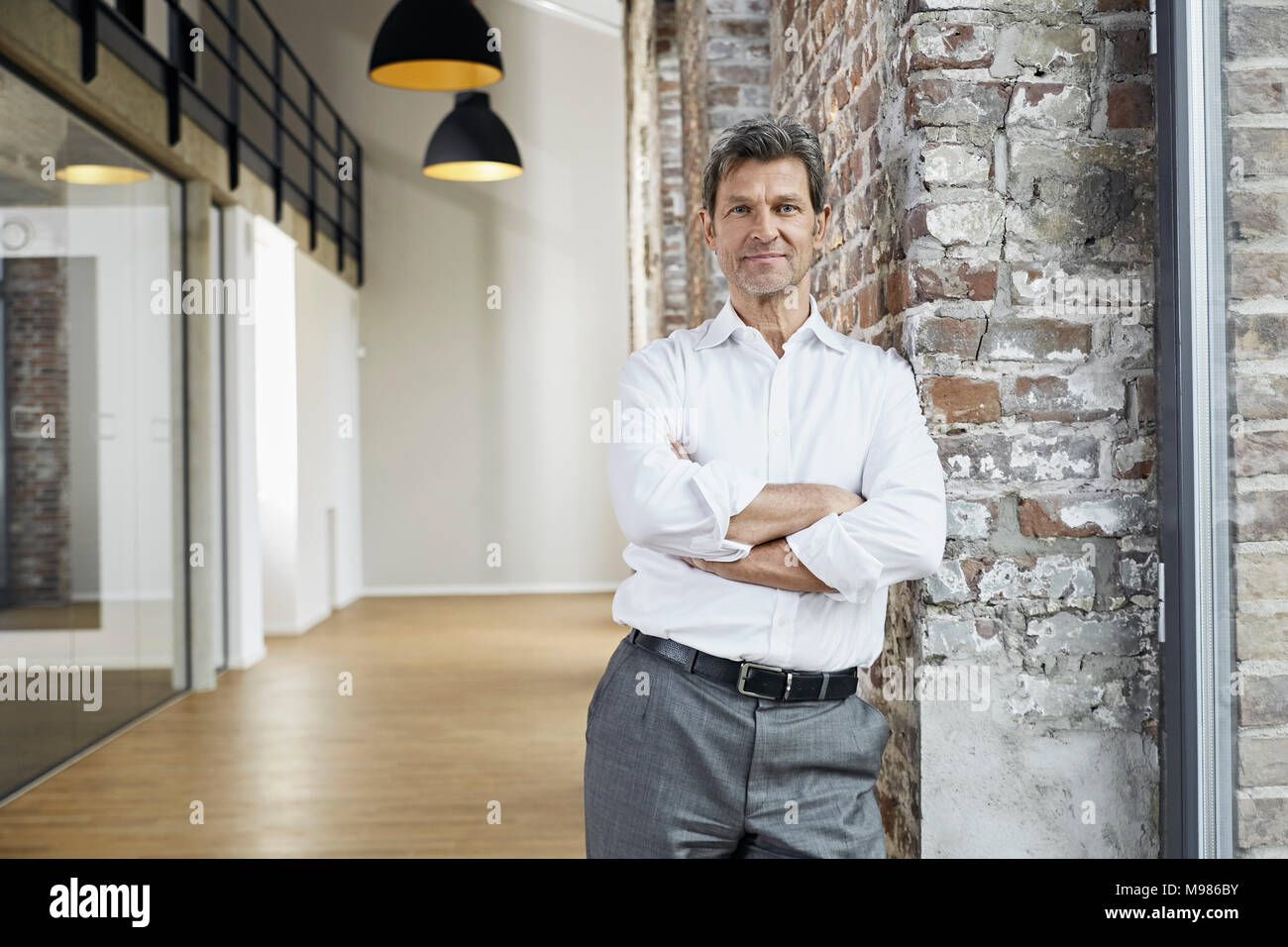 Portrait of confident businessman leaning against brick wall in modern office - Stock Image