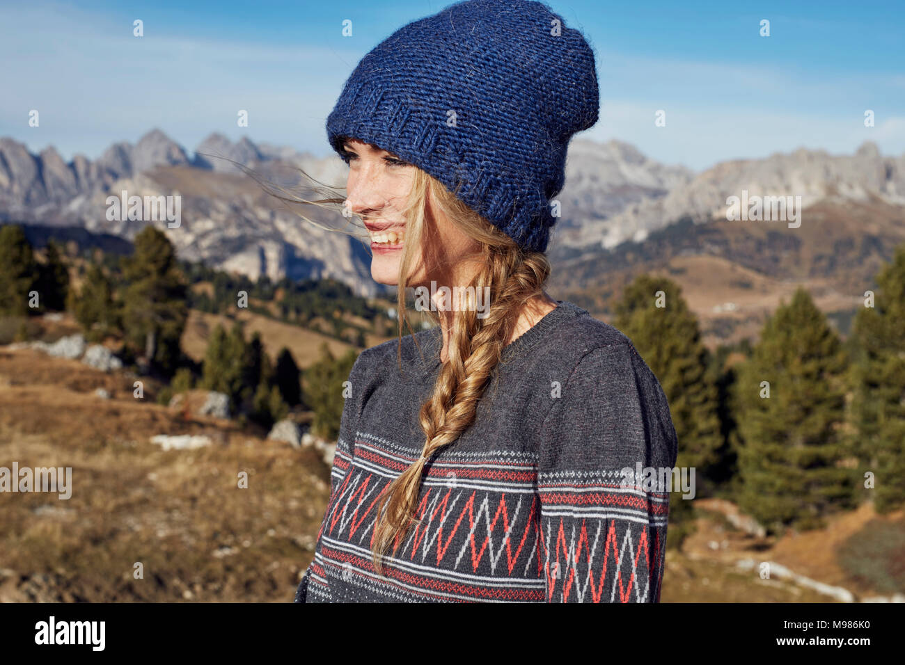 Portrait of happy young woman hiking in the mountains - Stock Image