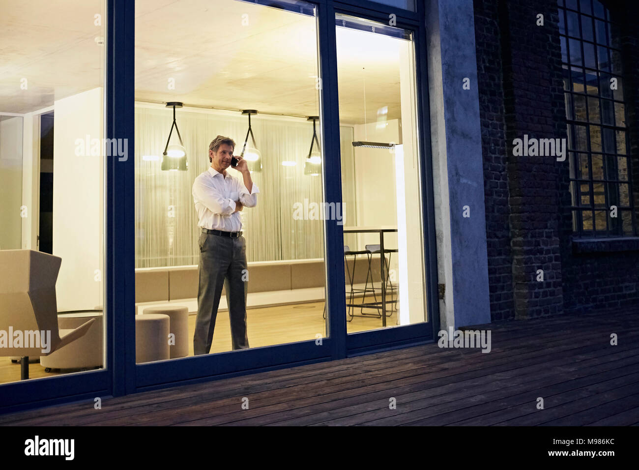 Exterior view of man using smartphone in modern building at night - Stock Image