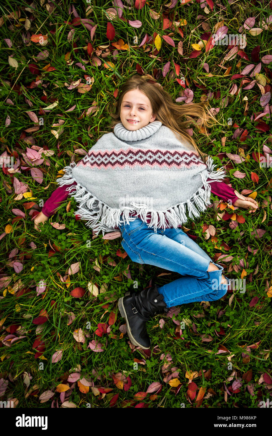Portrait of smiling girl wearing poncho lying on autumnal meadow - Stock Image