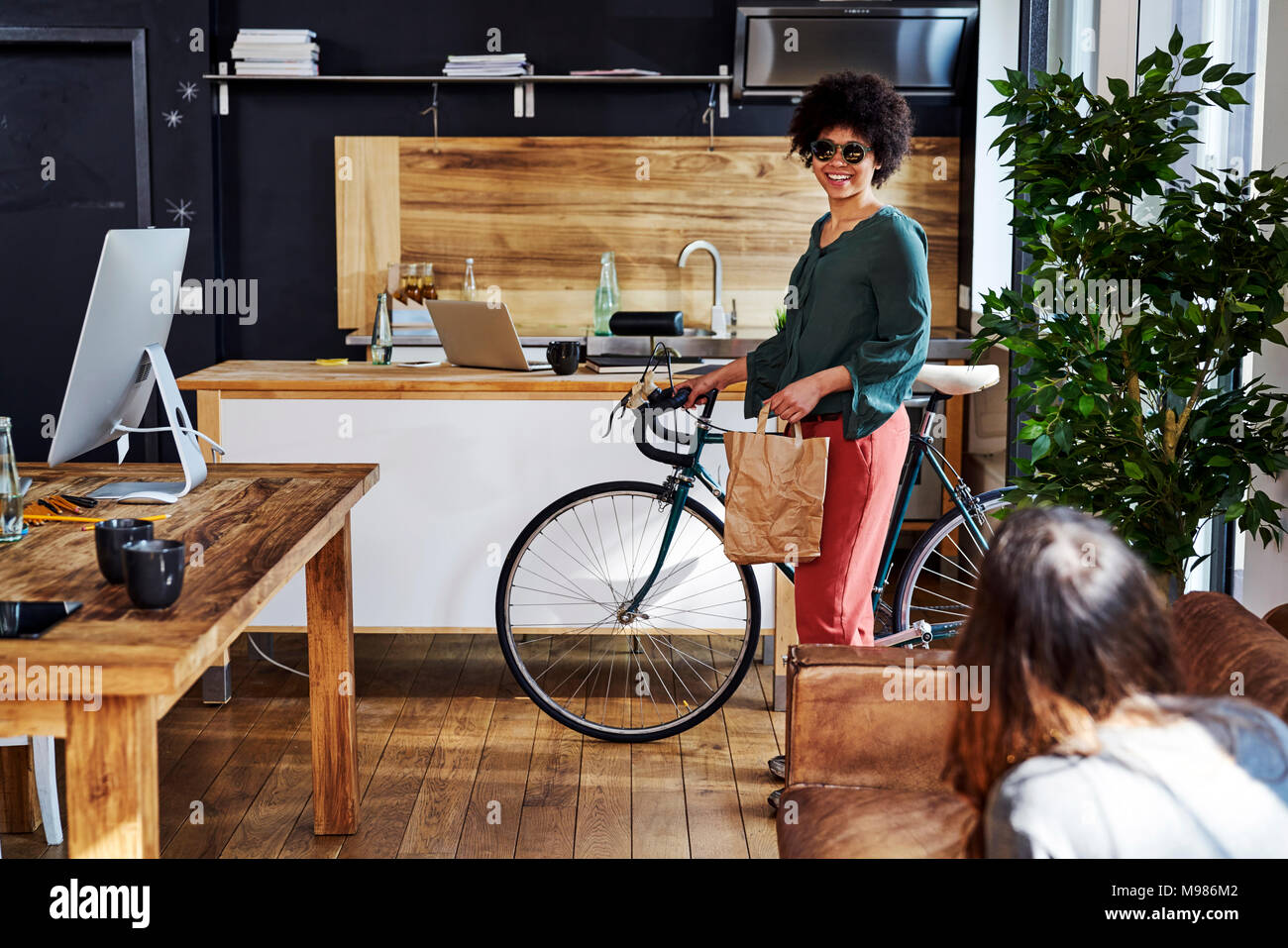 Young woman with bicycle arriving in modern office - Stock Image