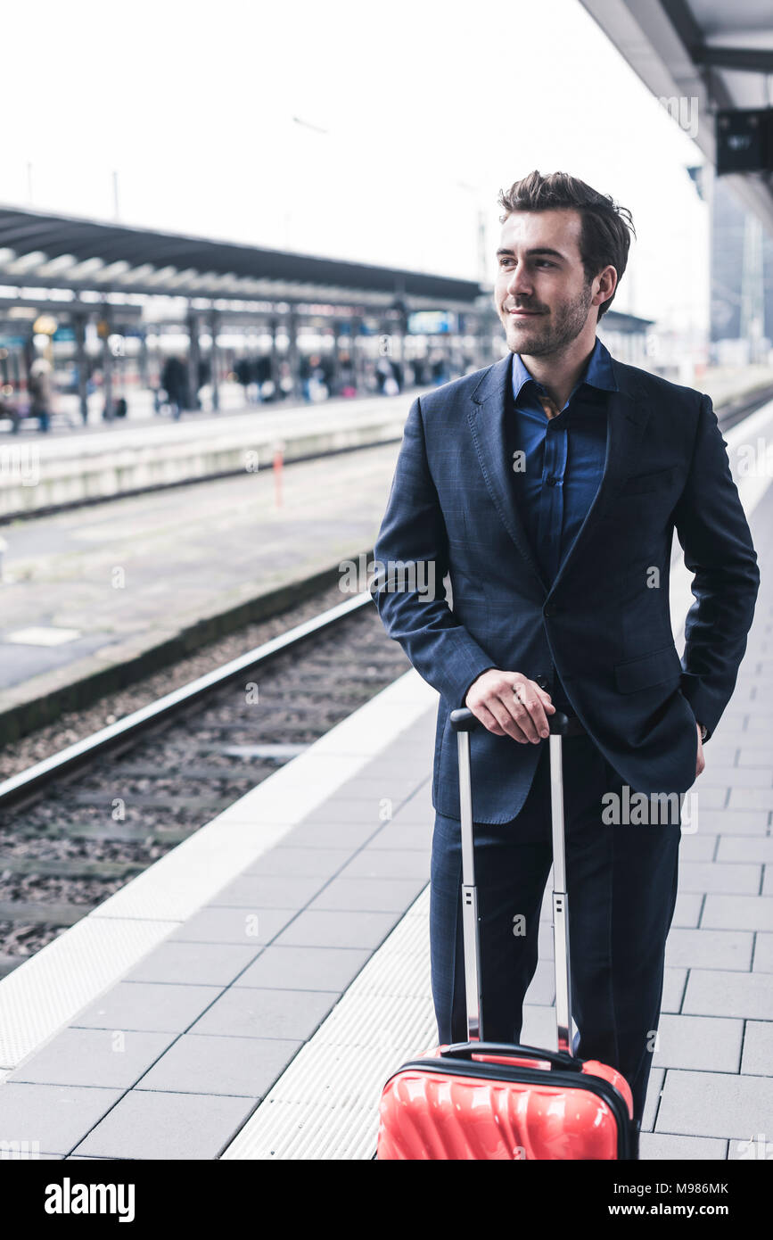 Young businessman waiting at station platform - Stock Image
