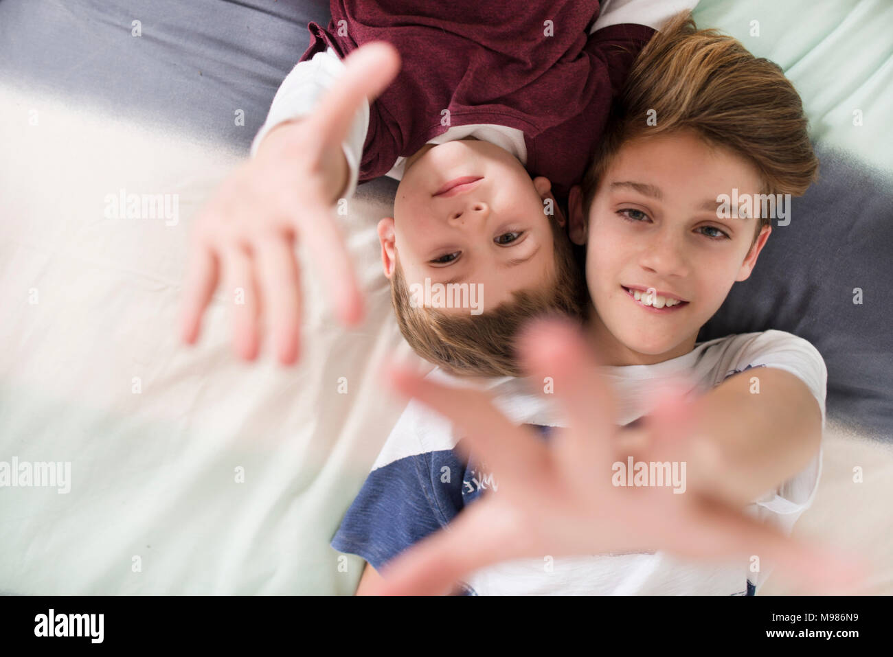 Top view of two smiling brothers lying on bed reaching out their hands - Stock Image