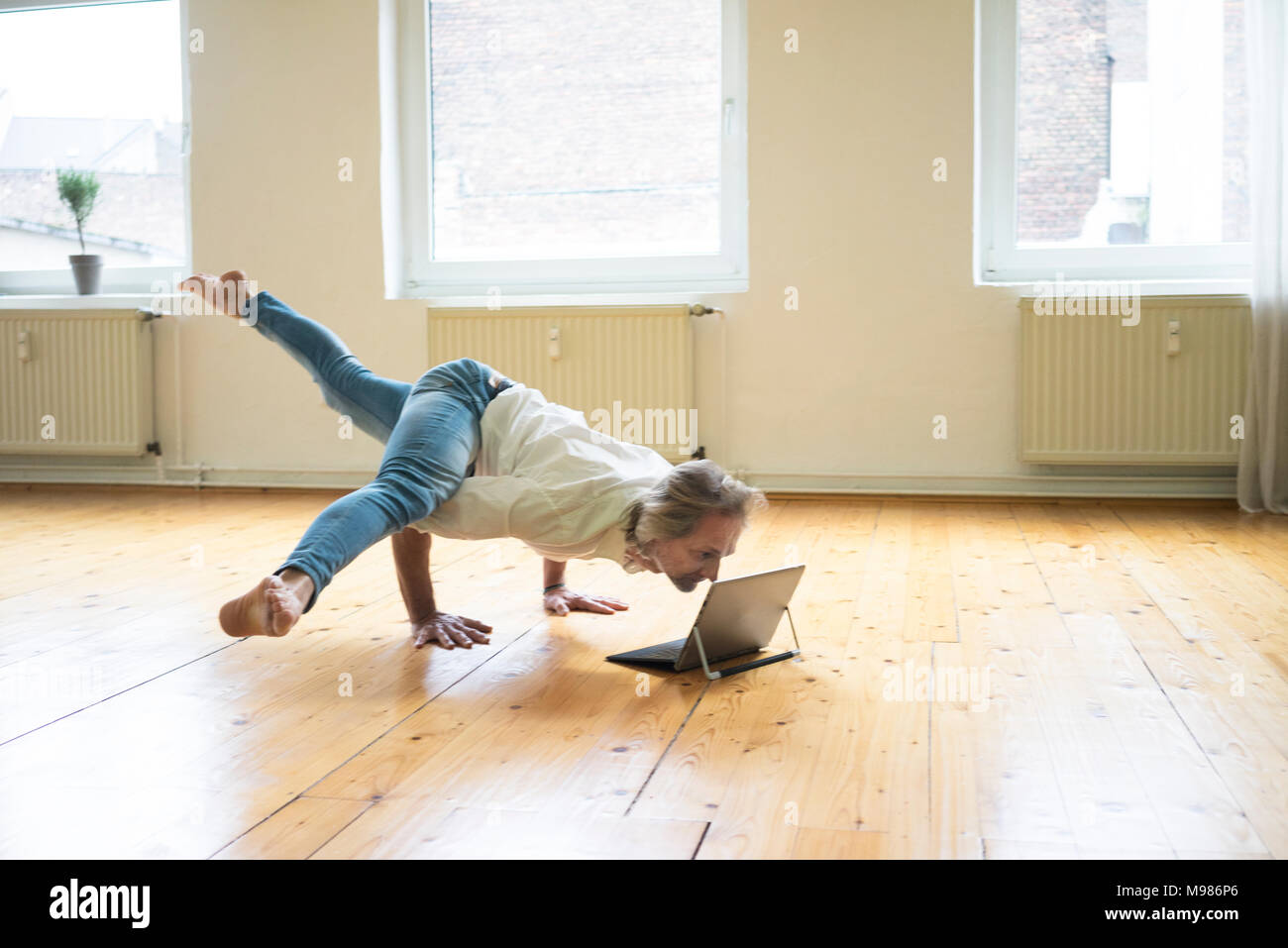 Mature man doing a handstand on floor in empty room looking at tablet - Stock Image