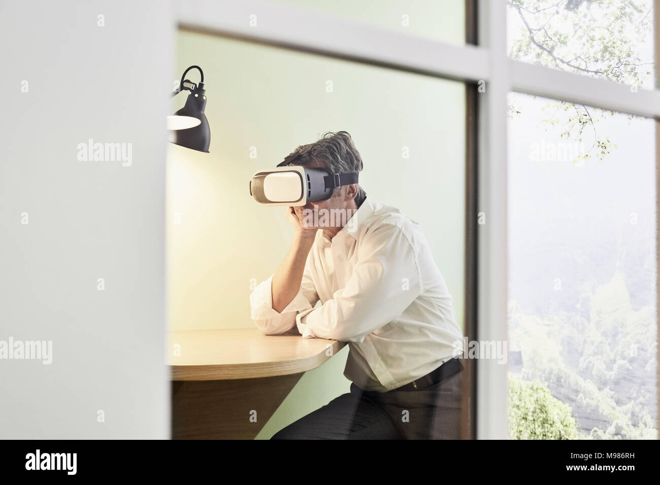 Businessman wearing VR glasses in modern office Stock Photo