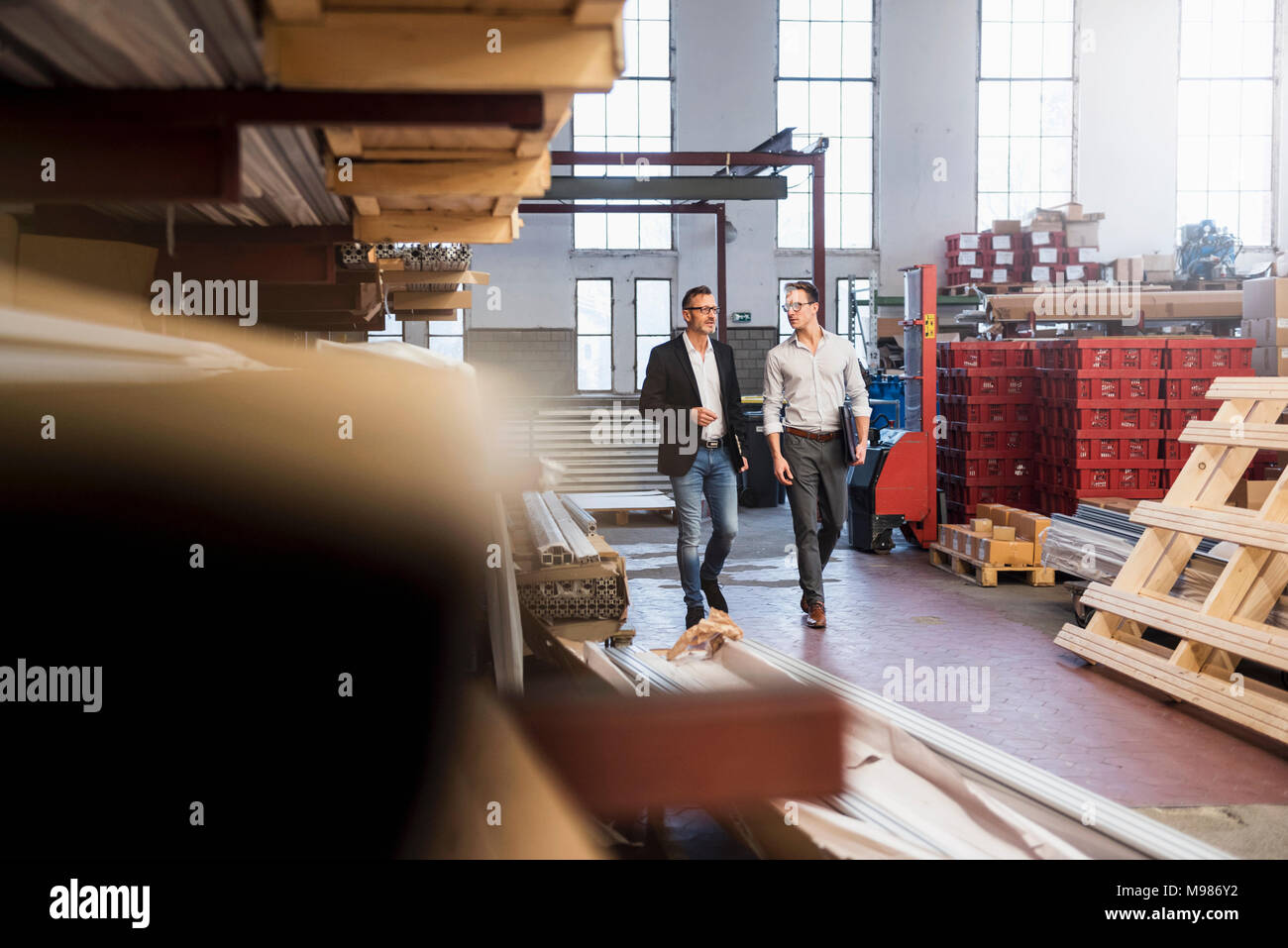 Two businessmen walking in factory storeroom - Stock Image