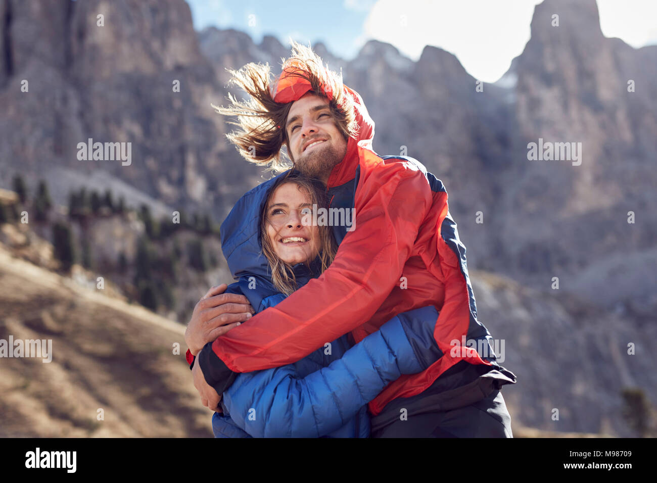 Happy young couple hugging in windy mountains - Stock Image