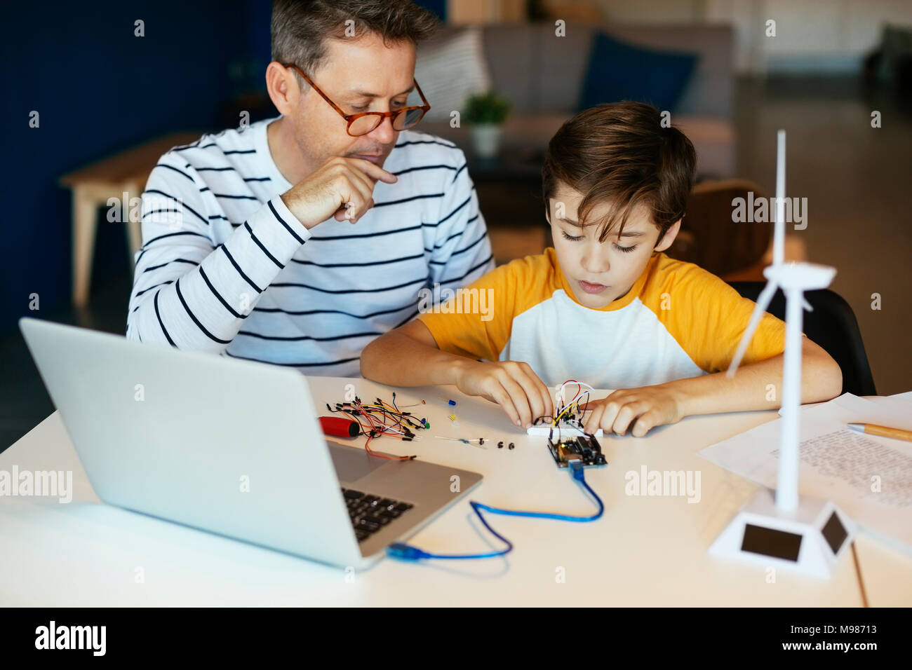 Father and son assembling a construction kit with laptop and wind turbine model - Stock Image