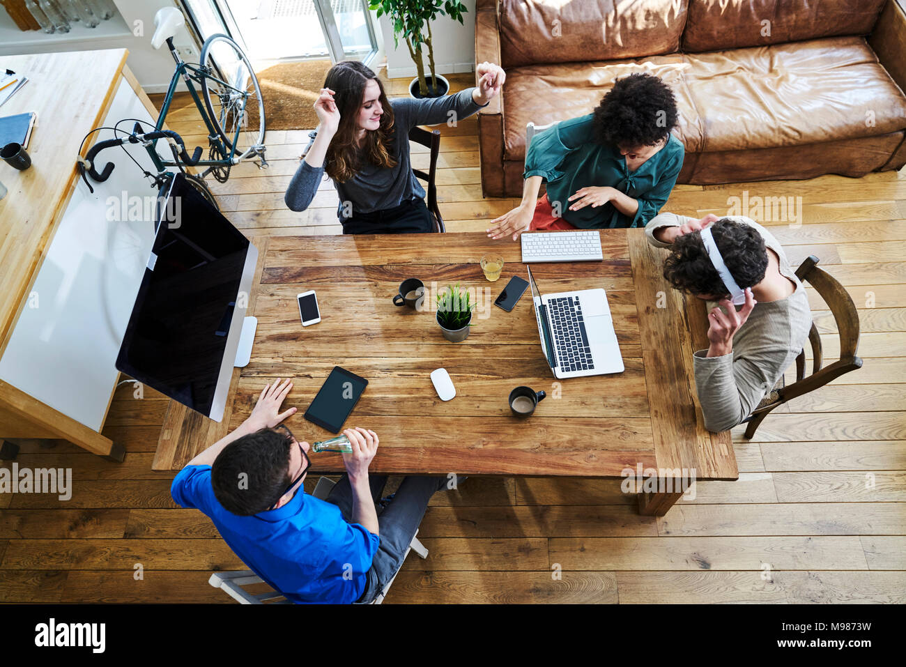 Elevated view of coworkers listening to music at wooden table in office - Stock Image