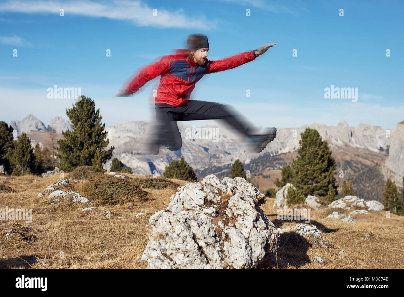 Young man jumping over rock in mountains - Stock Image