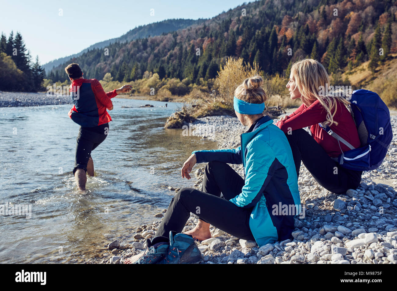 Group of friends hiking resting at the riverside - Stock Image