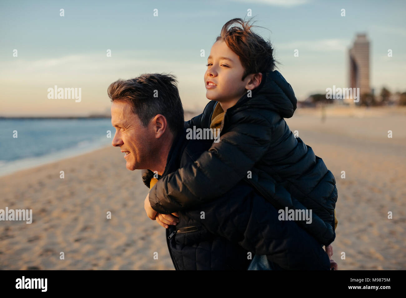 Father carrying son piggyback on the beach - Stock Image