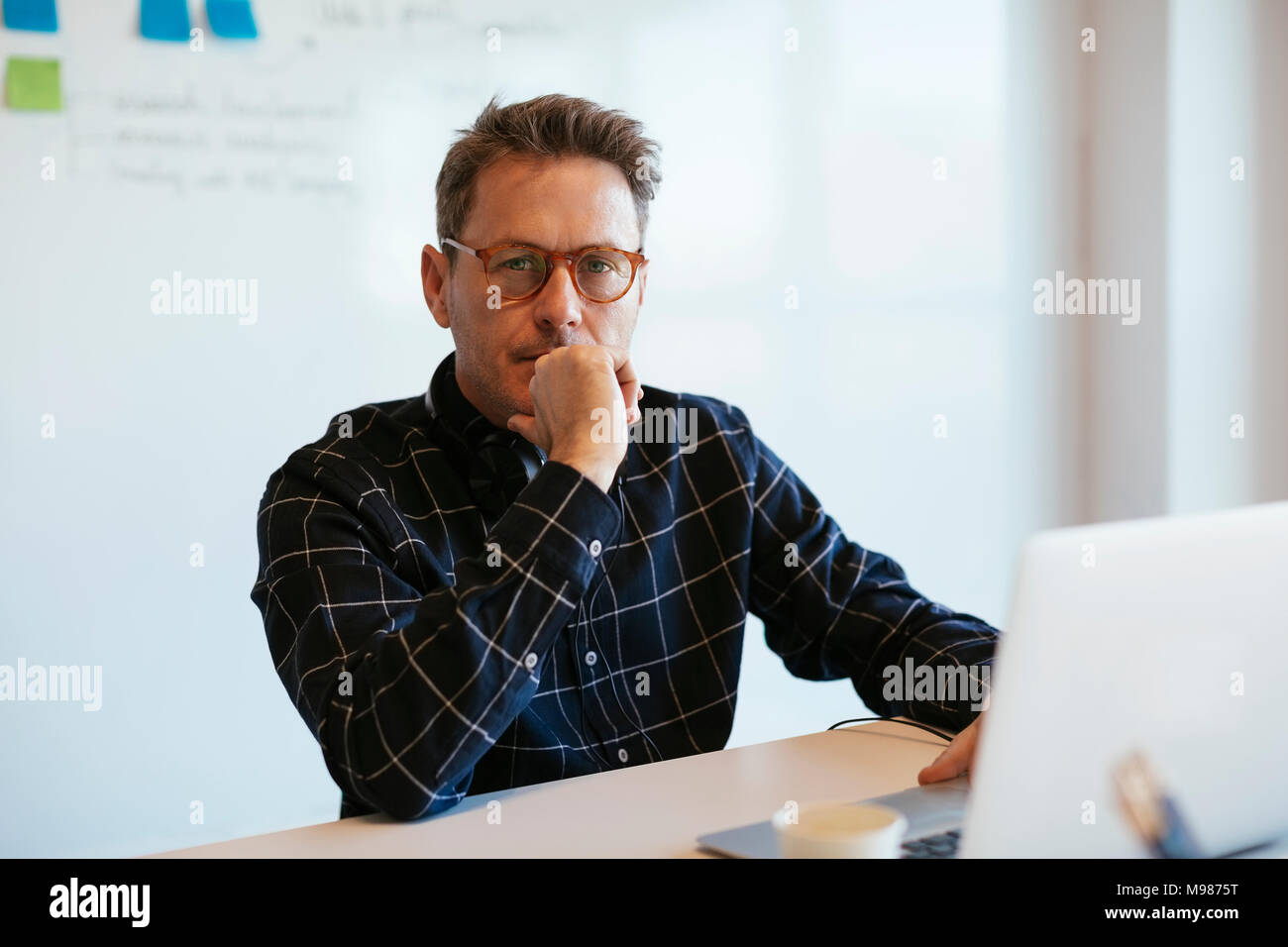 Portrait of serious businessman with laptop at desk in office - Stock Image