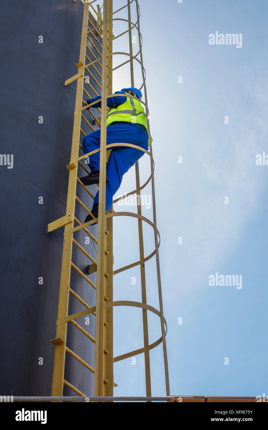 South Africa, Cape town, Construction worker climbing up ladder - Stock Image
