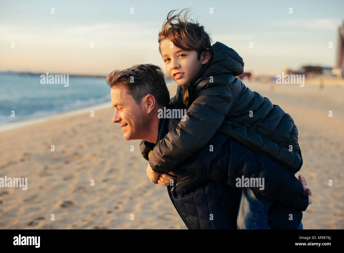 Portrait of father carrying son piggyback on the beach - Stock Image