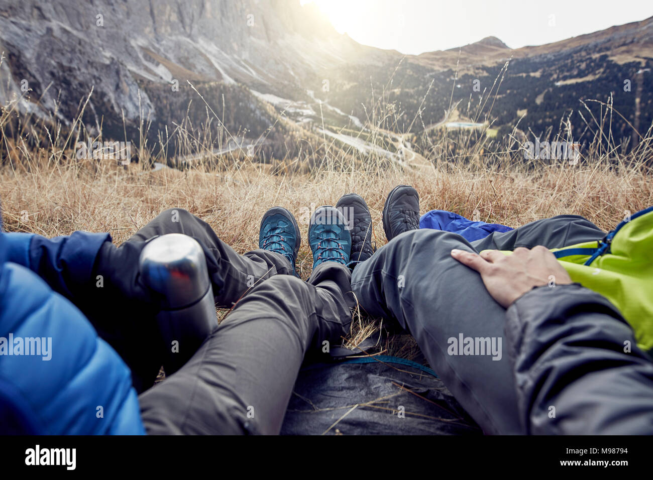 Legs of couple sitting in tent in the mountains - Stock Image
